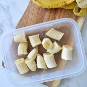 Banana bites in a container with banana peels on the side.