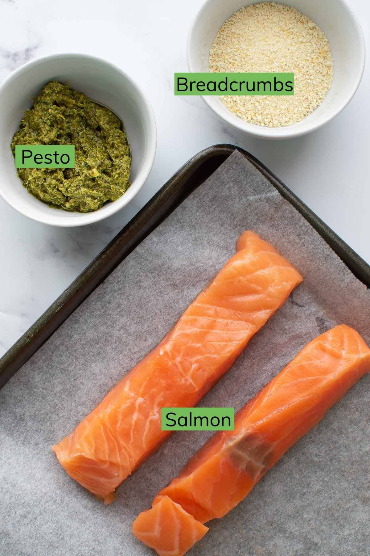 Salmon, pesto and breadcrumbs laid out on a table.
