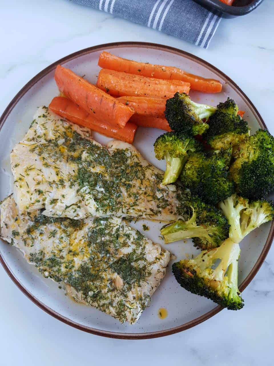 Herbed cod on a plate with roasted broccoli and carrots.