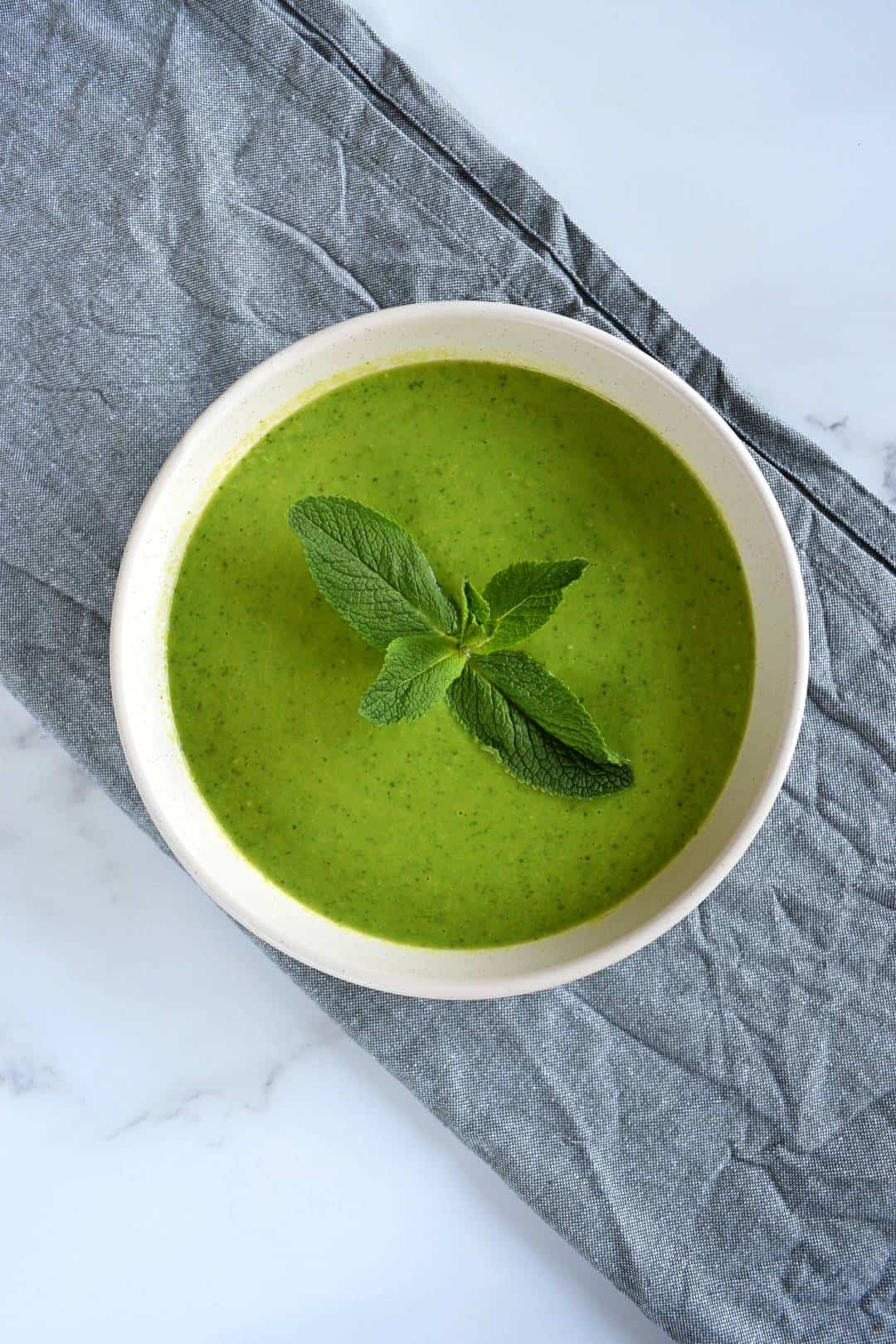 Minty pea soup in a white bowl with a sprig of mint on top.