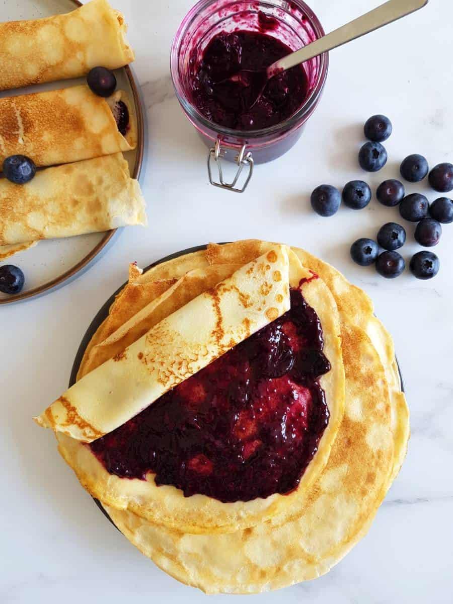 Blueberry jam spread on Norwegian pancakes.