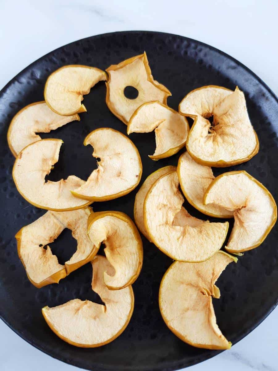 Oven baked apple slices on a black plate.