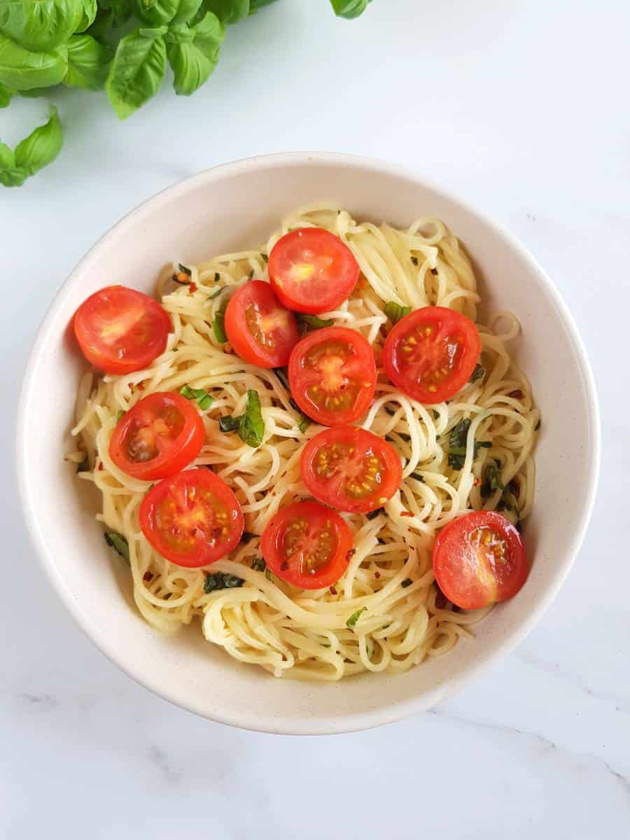 Noodles with basil and tomatoes in a bowl.