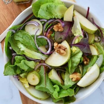 Pear and walnut salad with red onion in a bowl.