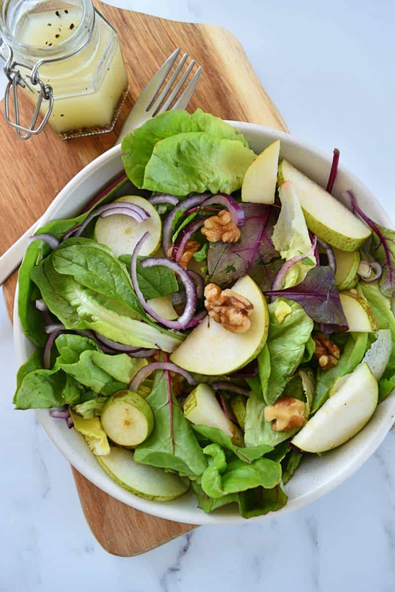 Pear and walnut salad in a bowl with dressing on the side.