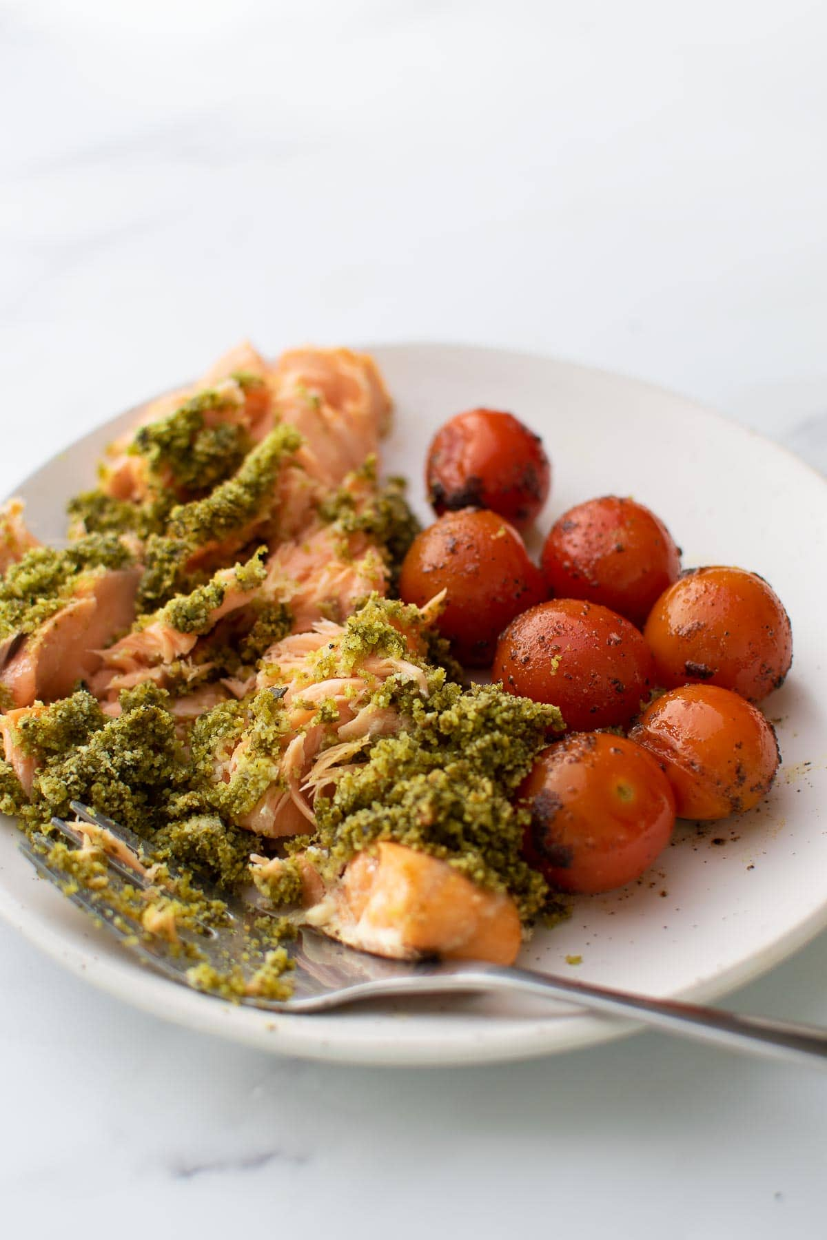 Smashed pesto crusted salmon on a plate with cherry tomatoes.
