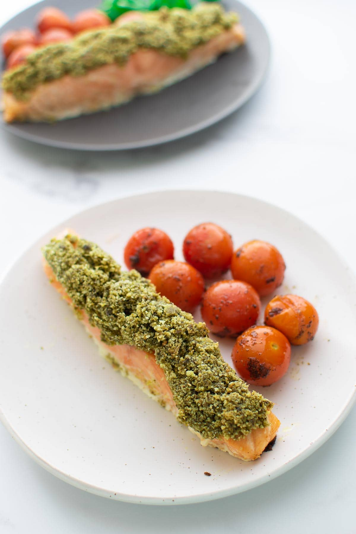 Pesto crusted salmon on a plate with cherry tomatoes on the side.
