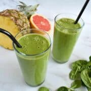 Pineapple grapefruit smoothie with fresh fruits and spinach on the side.