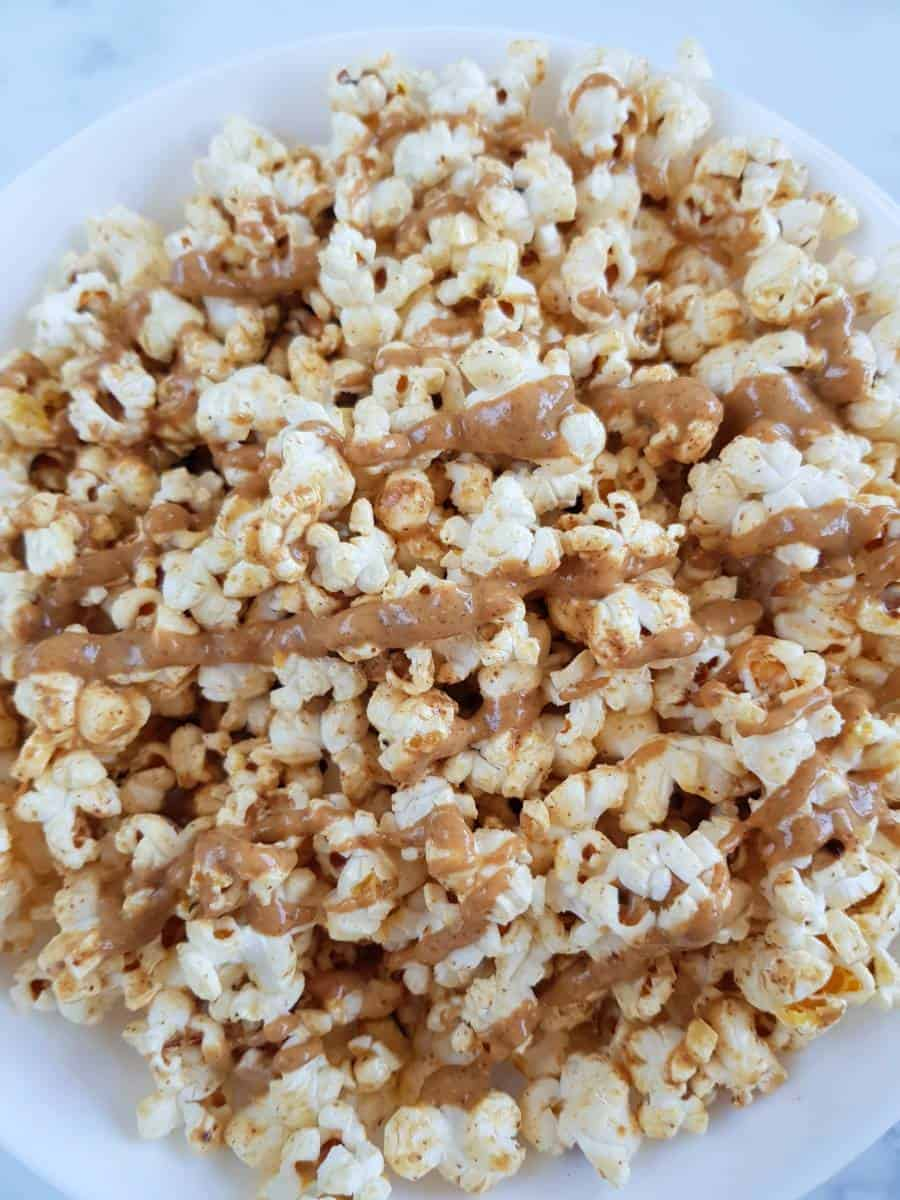 Popcorn with peanut butter drizzled on top.