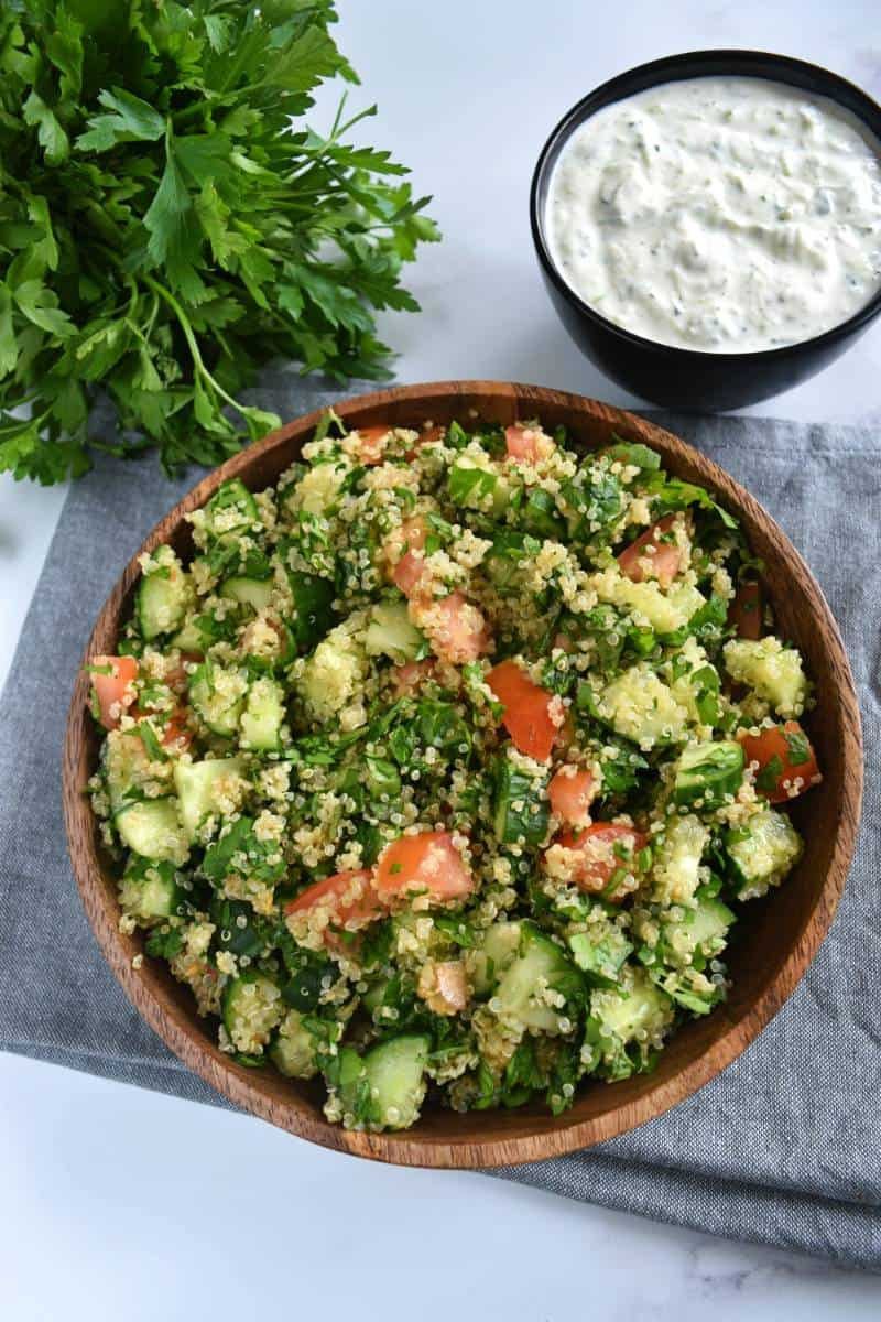 Quinoa tabbouleh with tzatziki and fresh herbs on the side.
