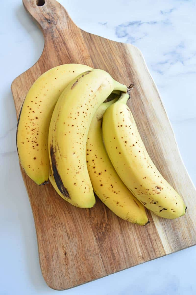 Ripe bananas on a wooden chopping board.