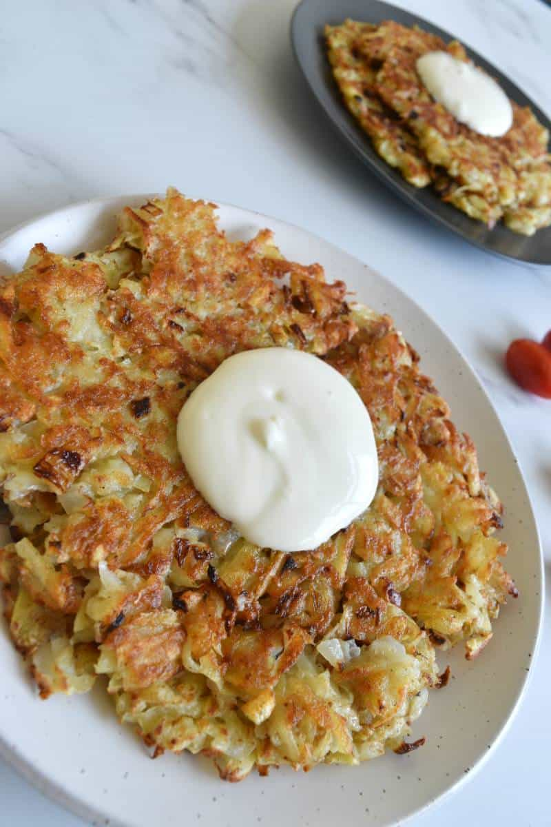 Russian potato pancakes on a plate on a marble table.