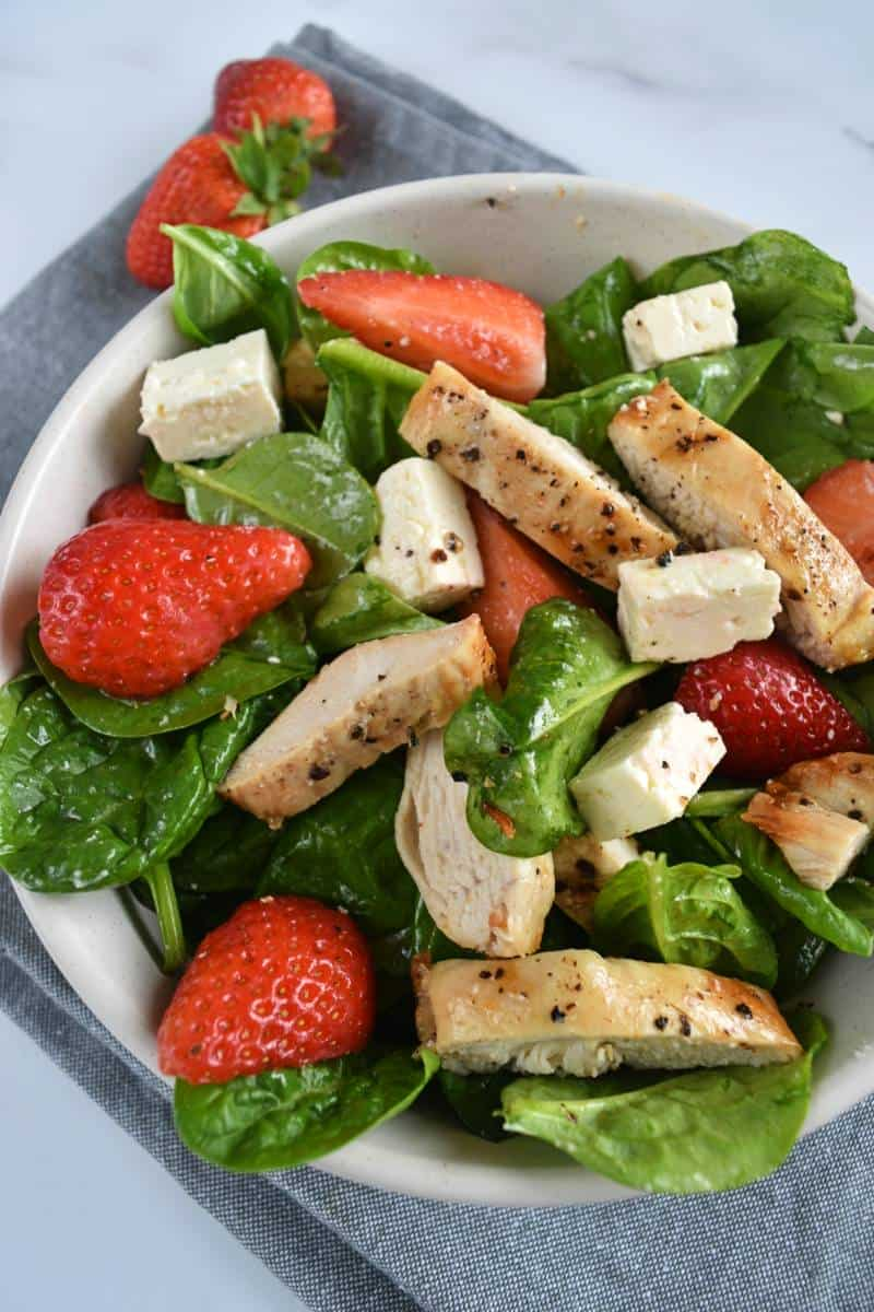 Salad with chicken feta and strawberries in a white bowl on a marble table.