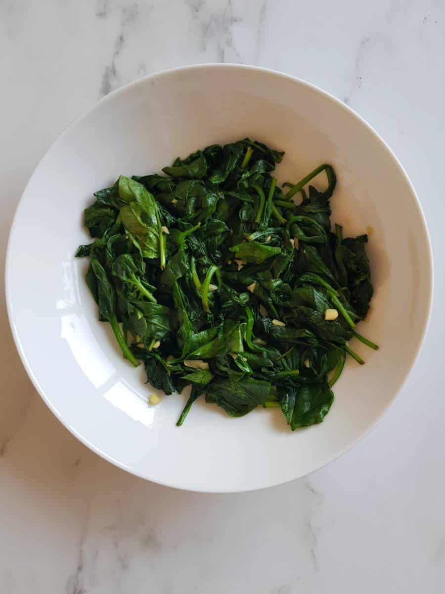 Sauteed spinach with garlic in a white bowl.