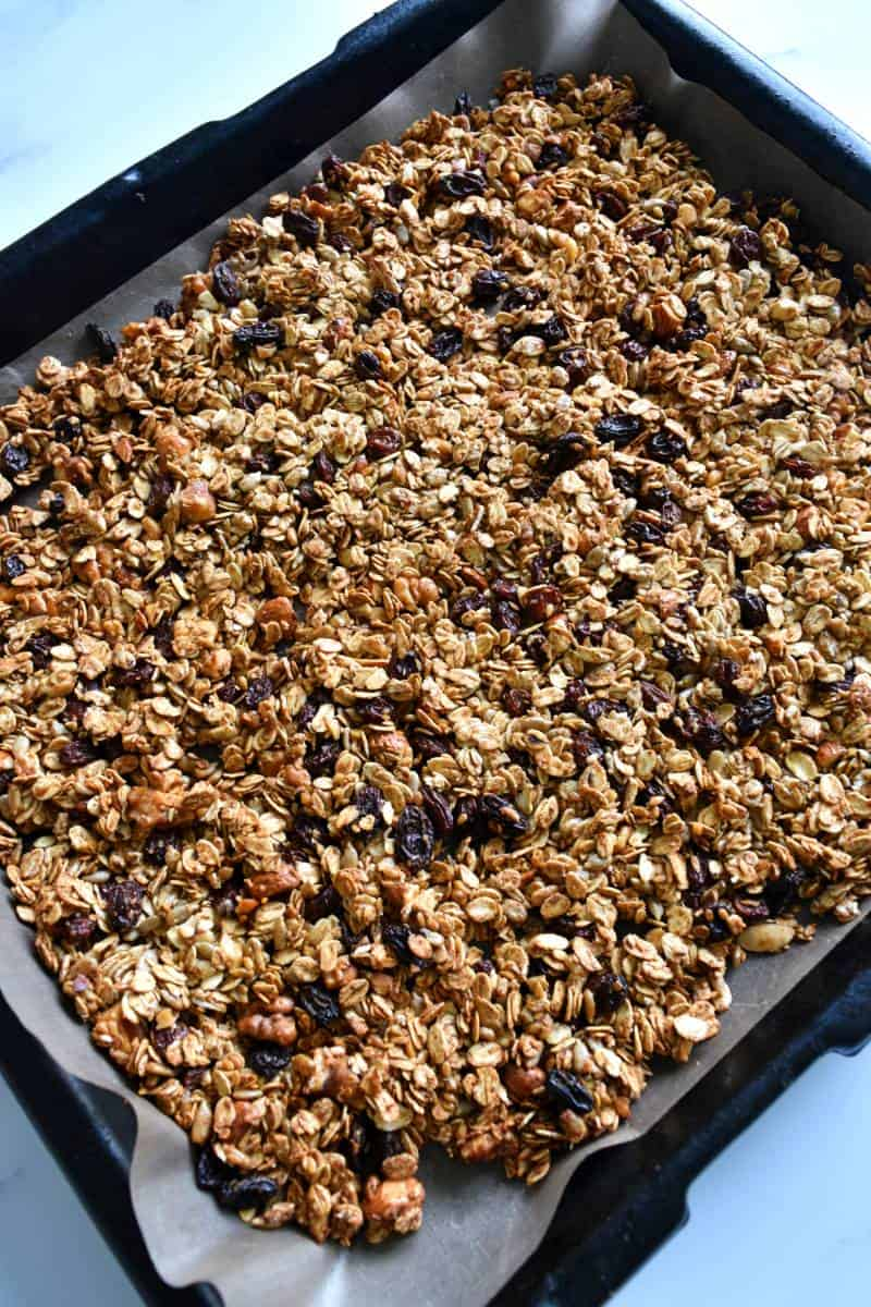 Granola spread out over a sheet pan.