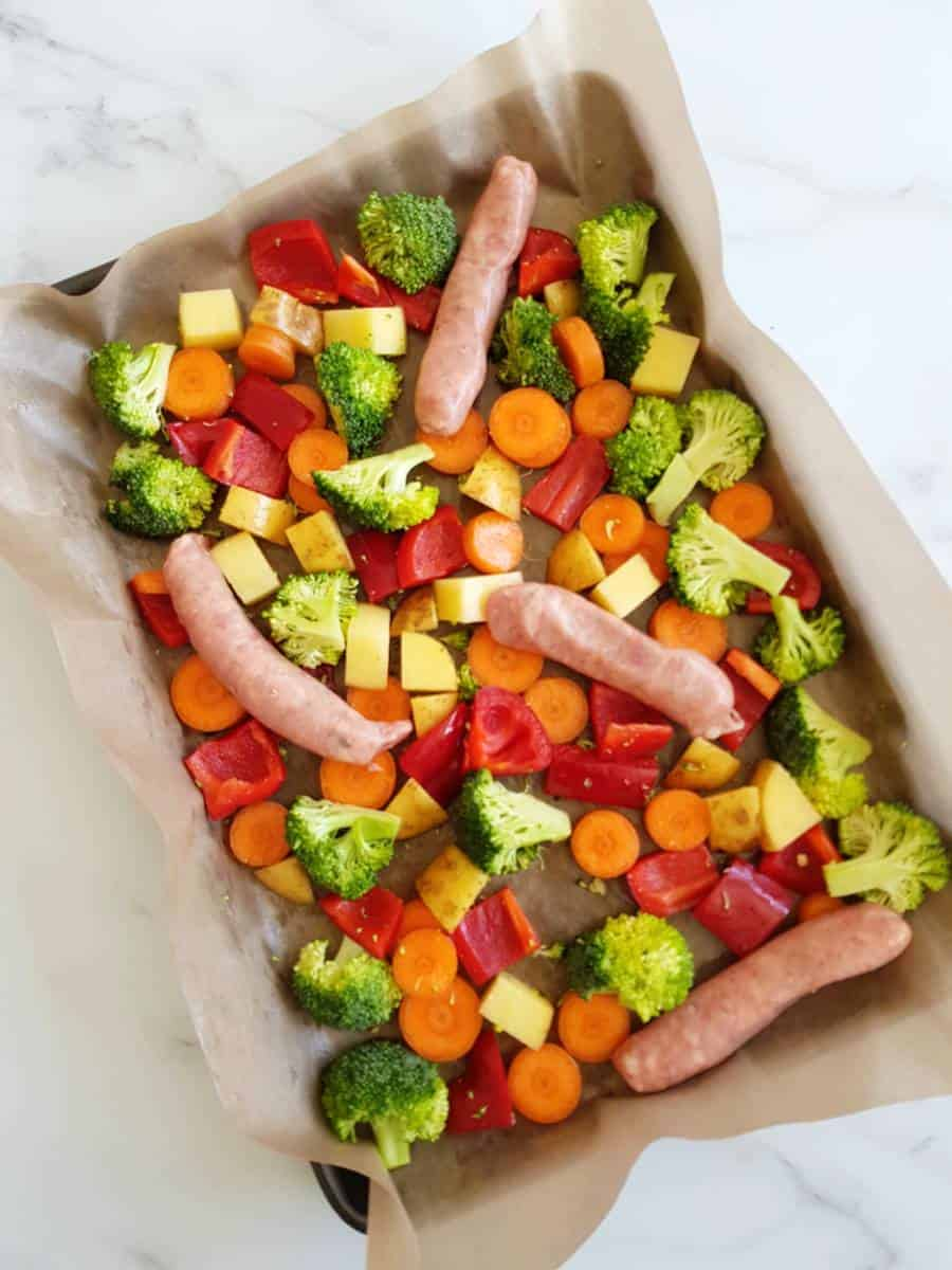 Sausages and vegetables on a sheet pan.