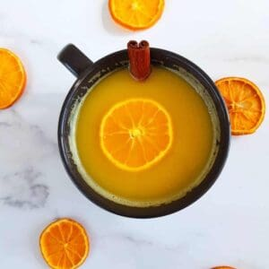 Spiced hot orange juice with cinnamon stick in a cup.