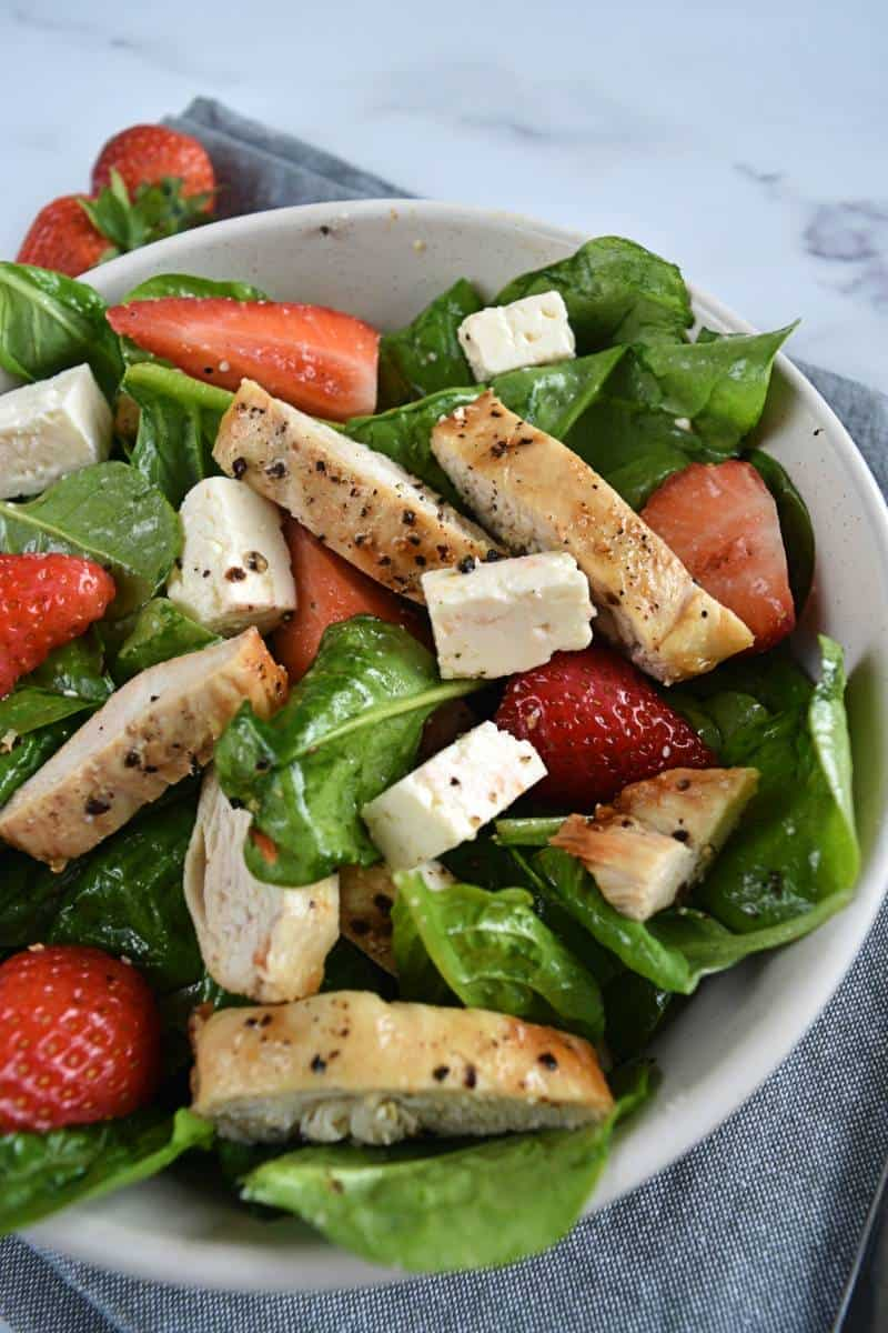 Spinach strawberry feta salad in a bowl with air fryer chicken.