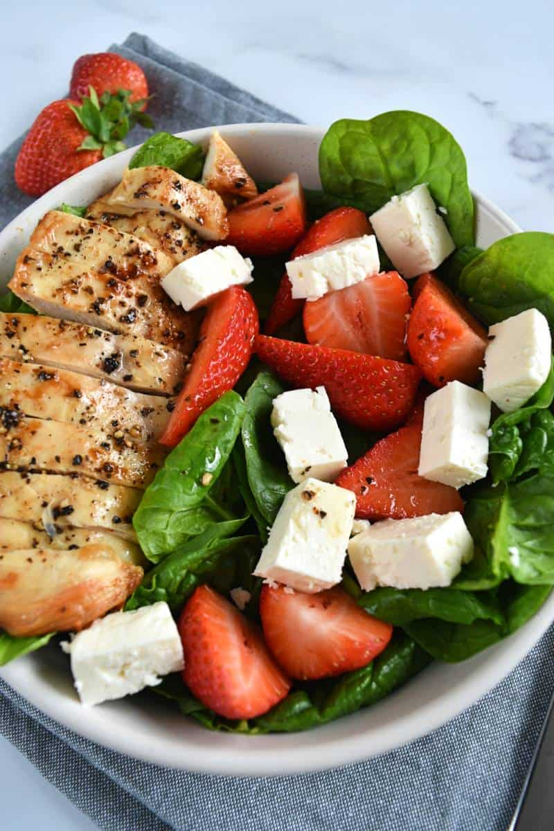 Strawberry salad with chicken in a bowl.