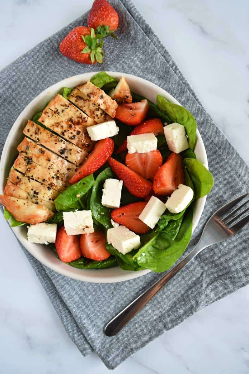 Strawberry spinach chicken salad in a bowl with a fork on the side.