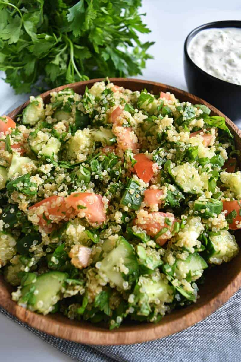 Tabbouleh with quinoa in a wooden bowl with fresh parsley in the background.
