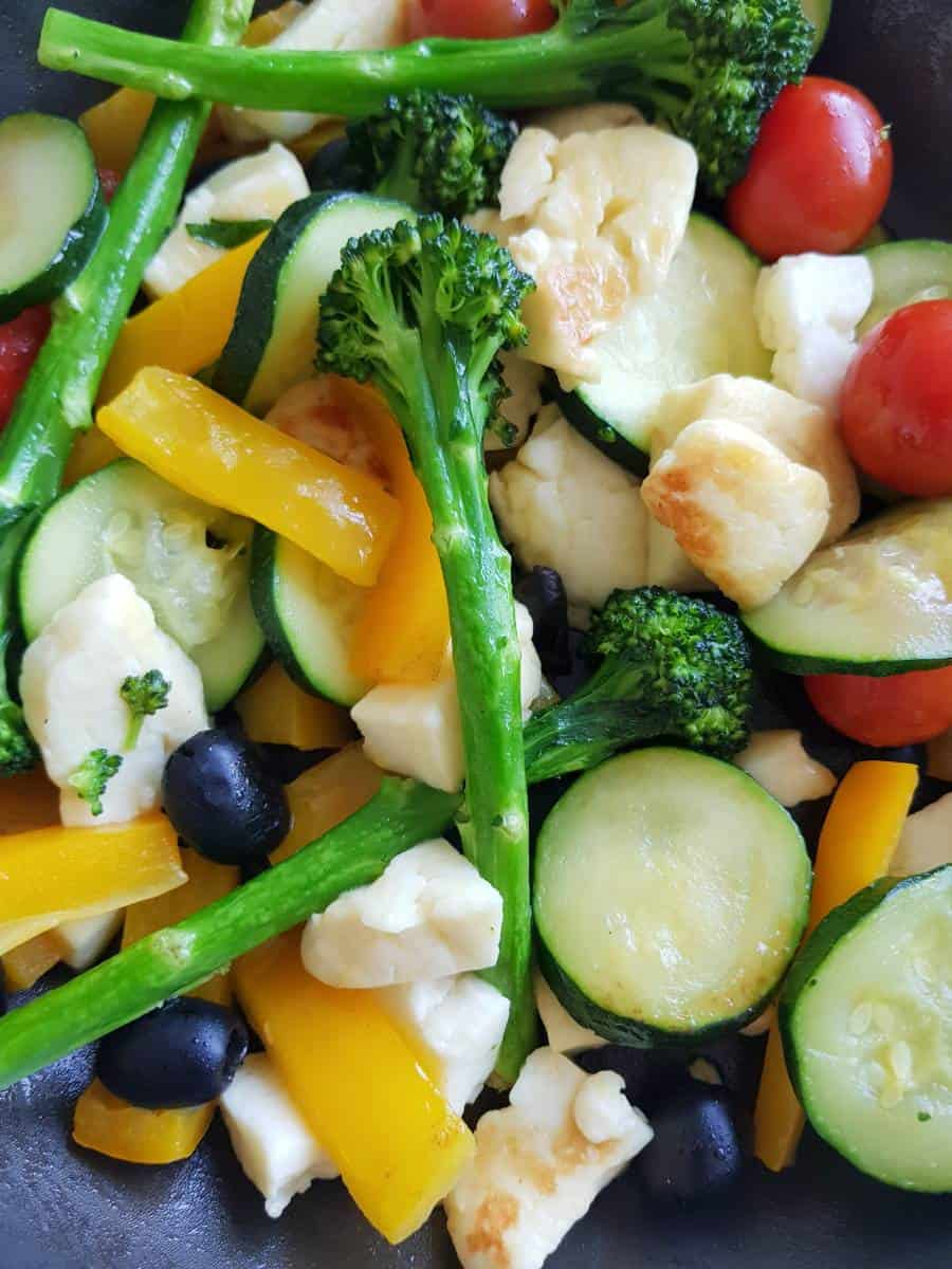 Halloumi and vegetables in a frying pan.