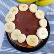 Banana pancakes stacked with bananas on top.