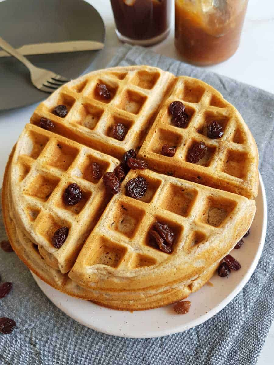 Waffles on a plate with raisins on top.