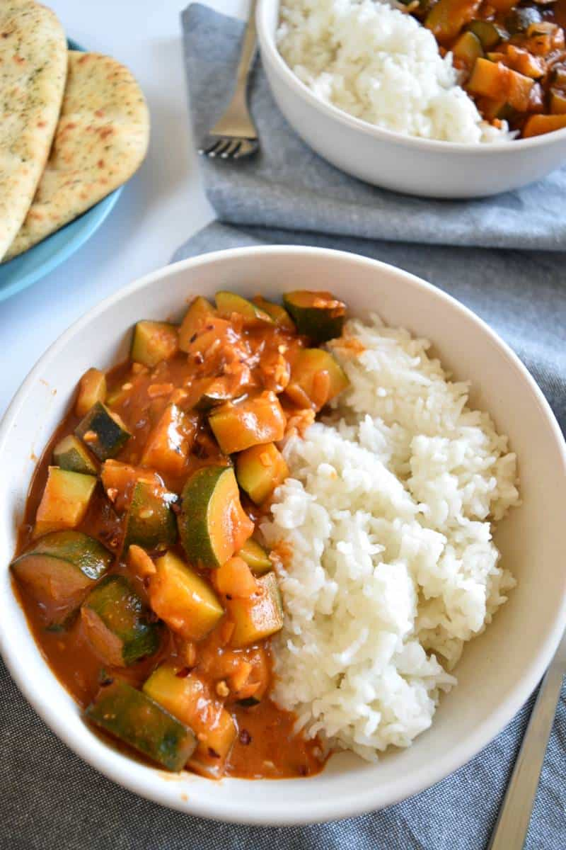Zucchini curry in a white bowl with rice.