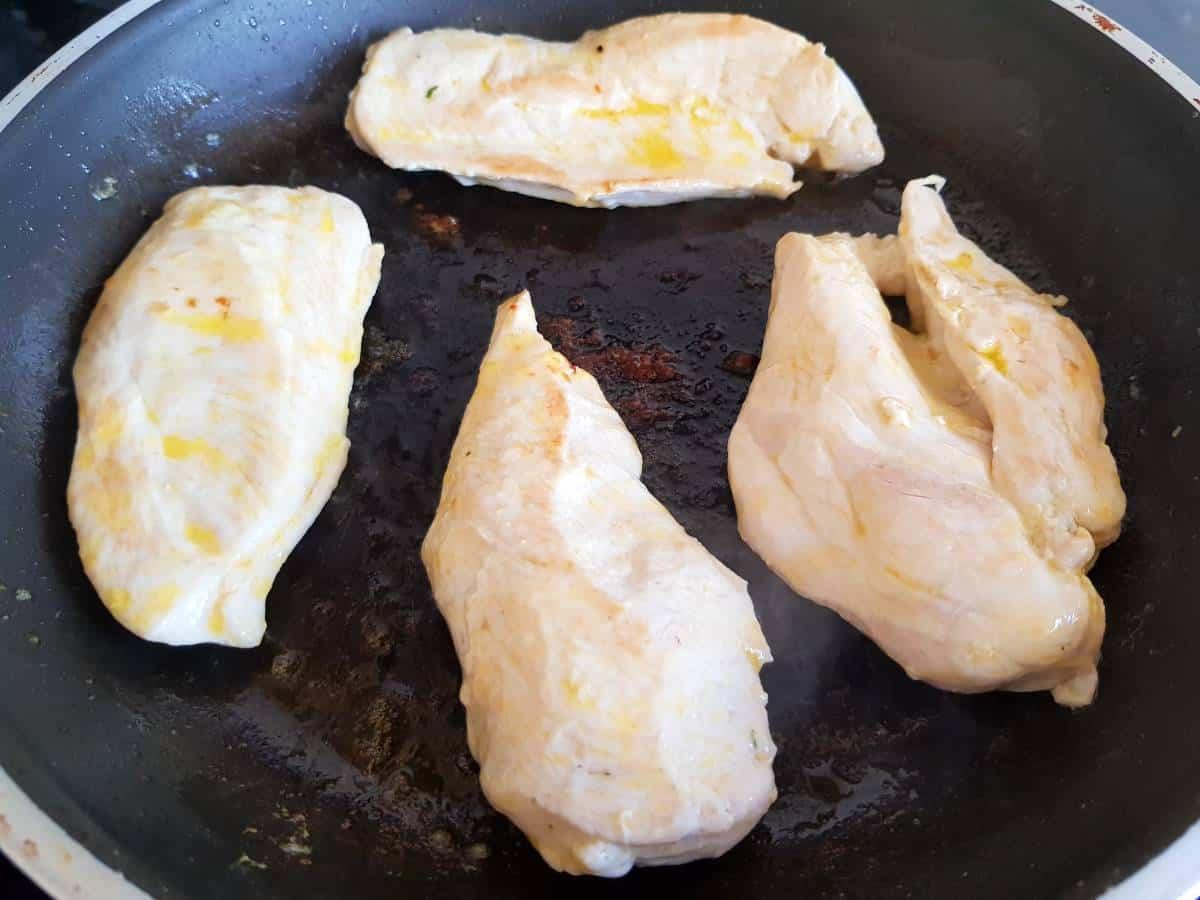 Chicken fillets in a pan.
