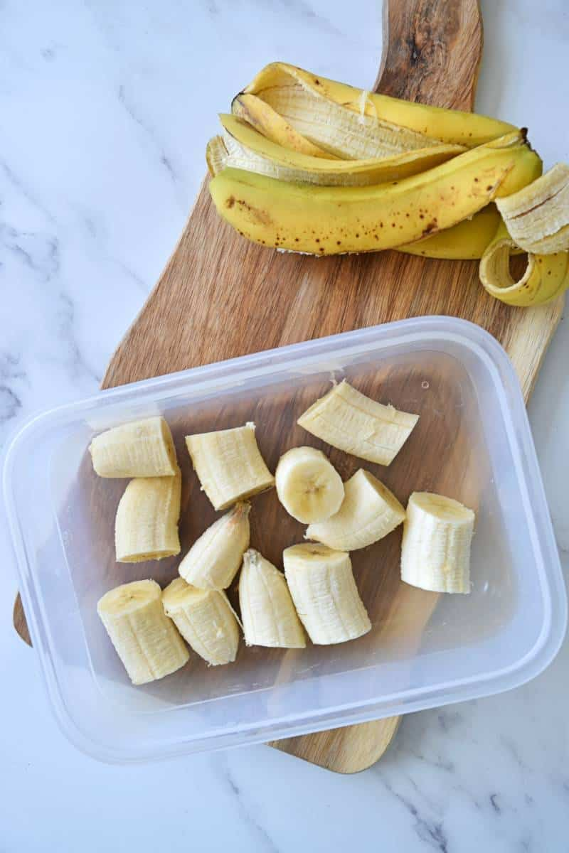 Diced bananas in a storage container with banana peels in the background.