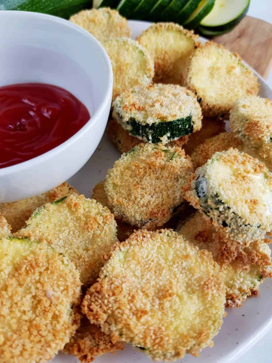 Breaded zucchini on a plate with dip.