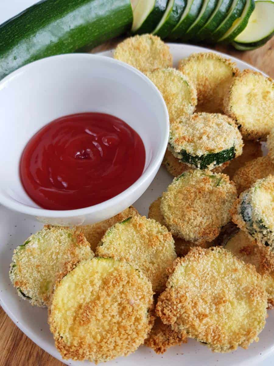 Crispy zucchini slices on a plate with ketchup.