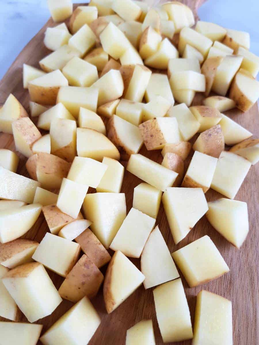 Diced potatoes on a chopping board.