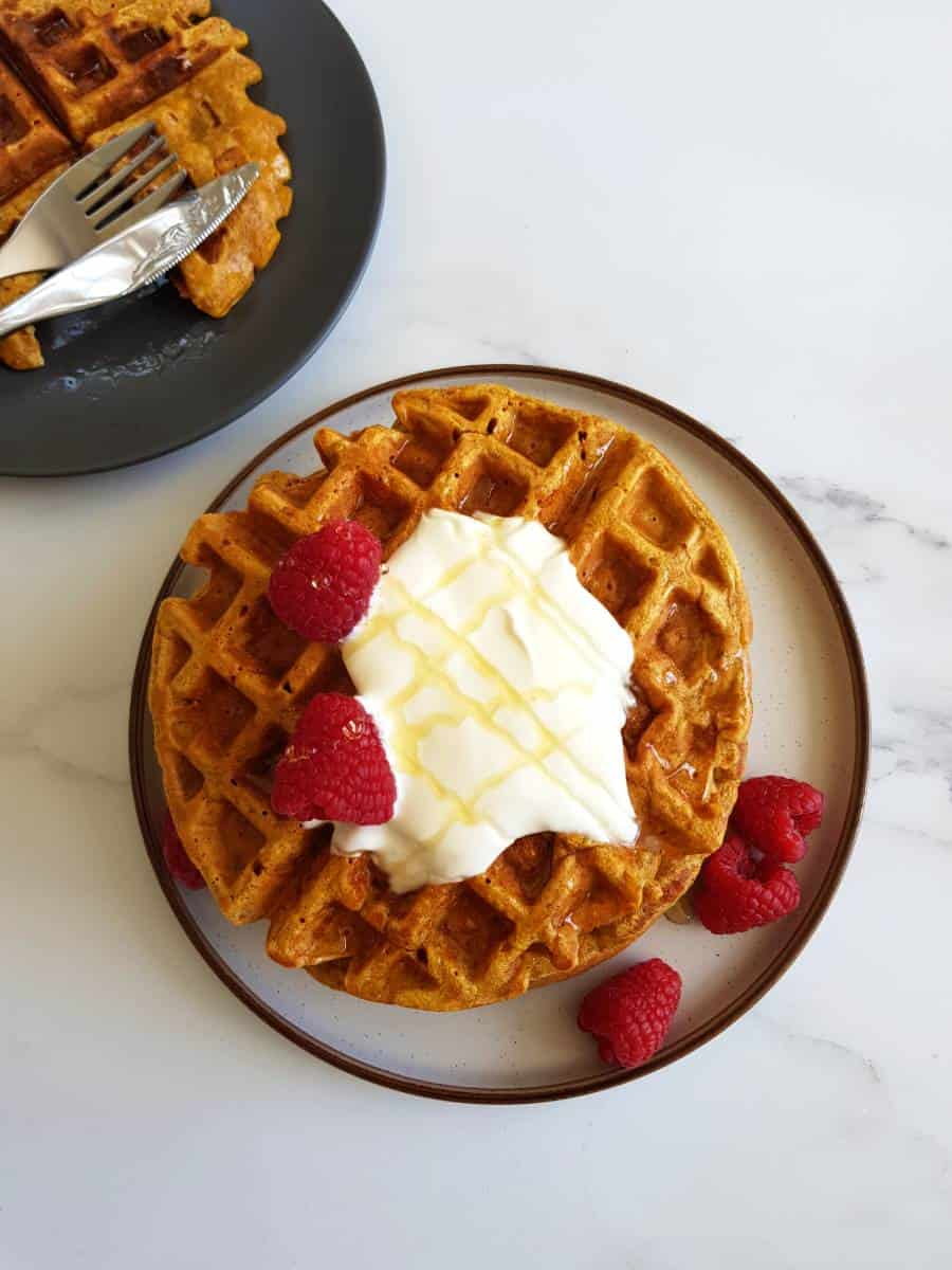 Golden butternut squash waffles on a plate.