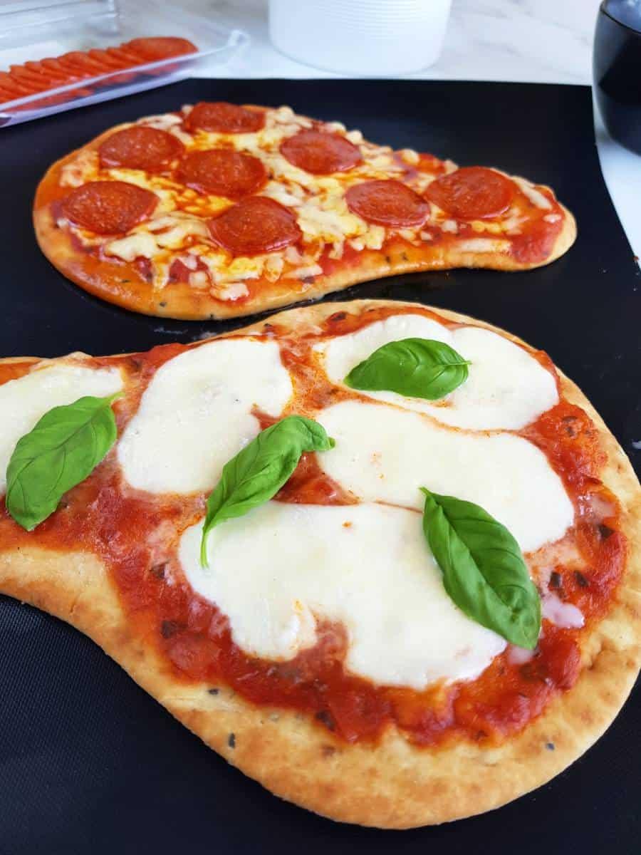 Margherita naan pizza on a baking sheet.
