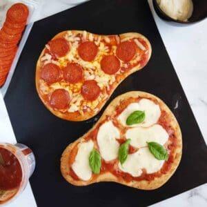 Naan bread pizzas on a baking sheet.