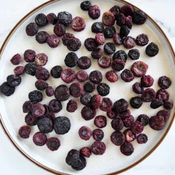 Oven dried blueberries on a plate.