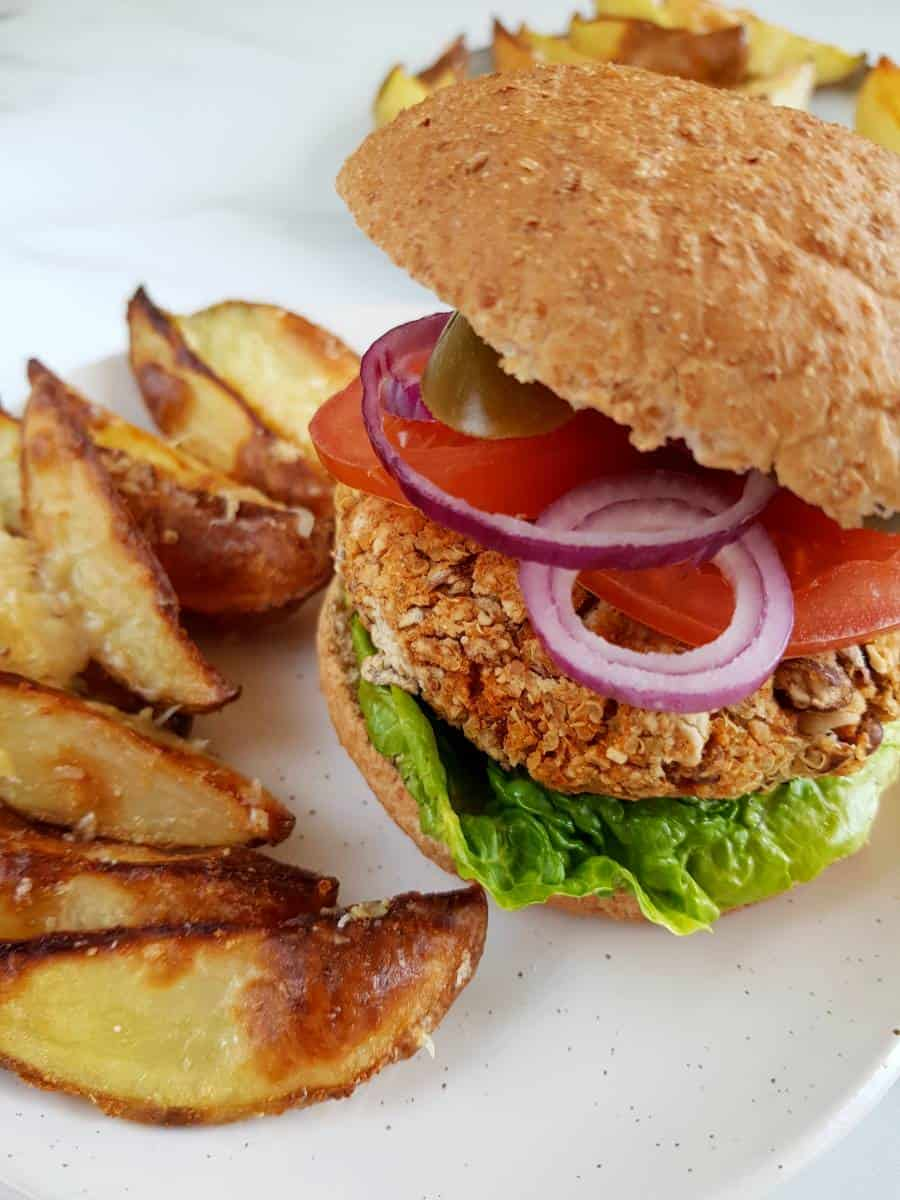 Pinto bean burger and potato wedges on a plate.