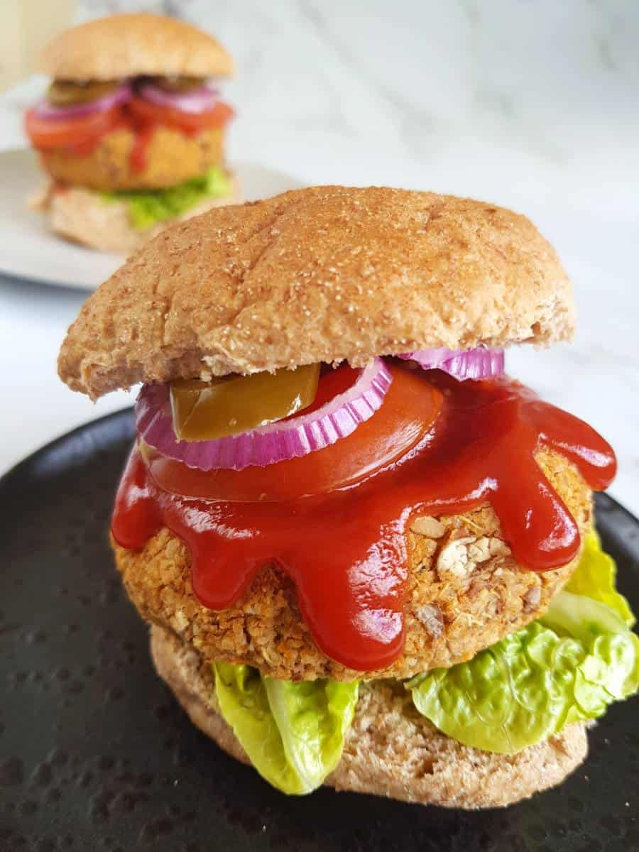 Pinto bean burger in a bun with lettuce, tomato, onions and ketchup.