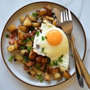 Pyttipanna on a plate with cutlery on the side.