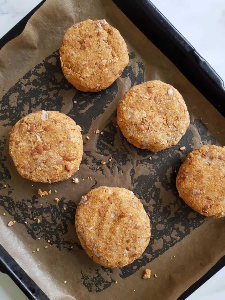 Uncooked pinto bean burgers on a sheet pan.
