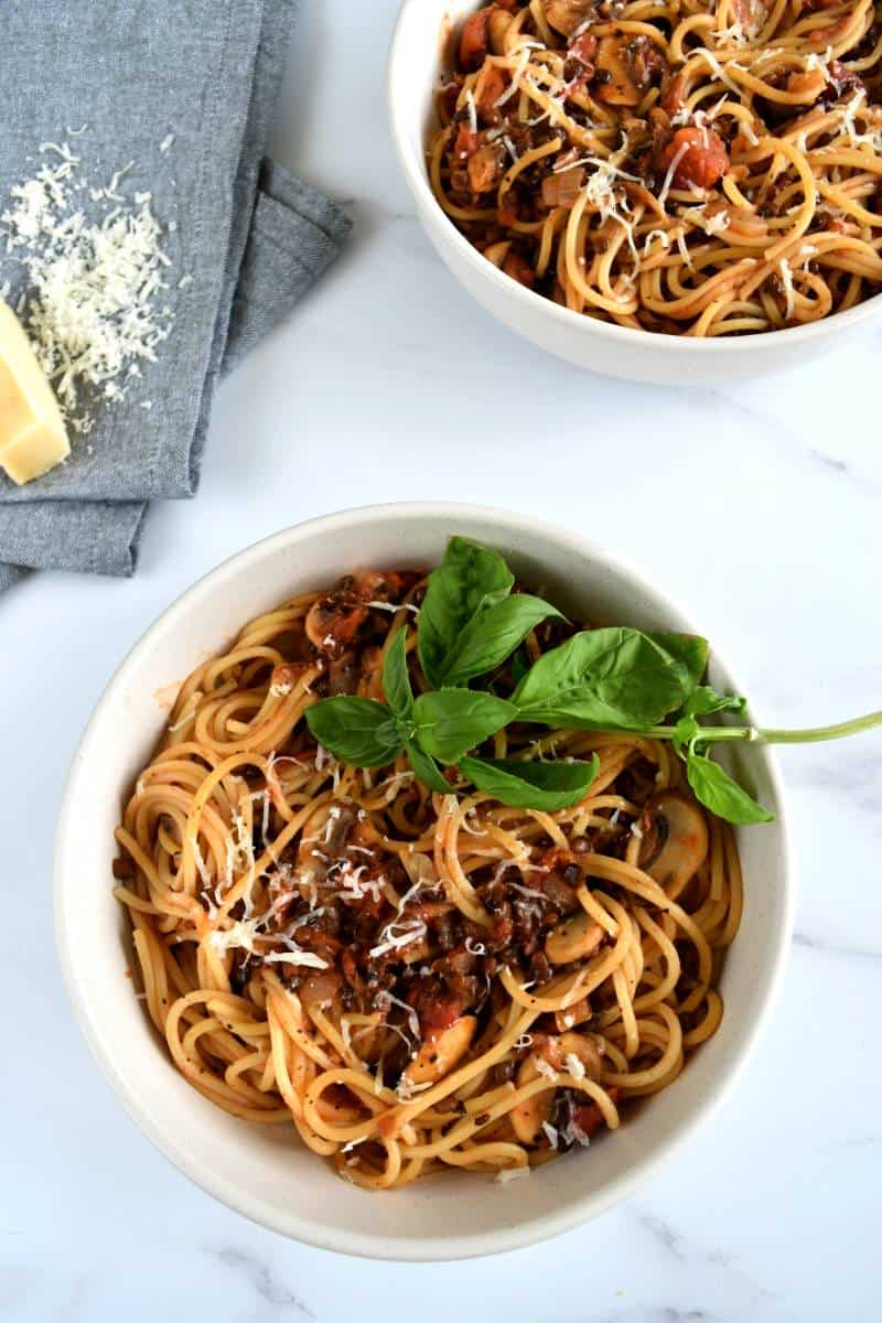 Vegetarian lentil bolognese in bowls with spaghetti and parmesan.
