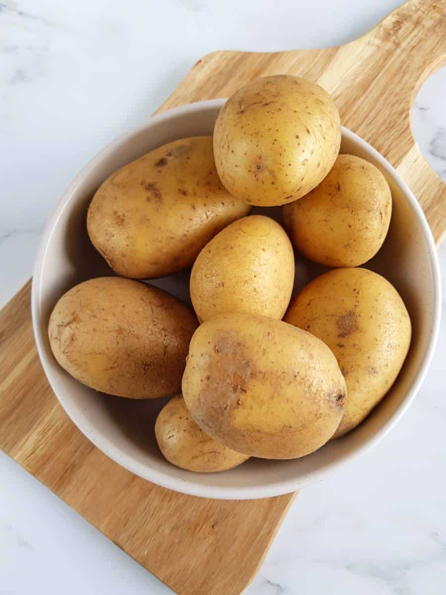 Whole potatoes on a chopping board.