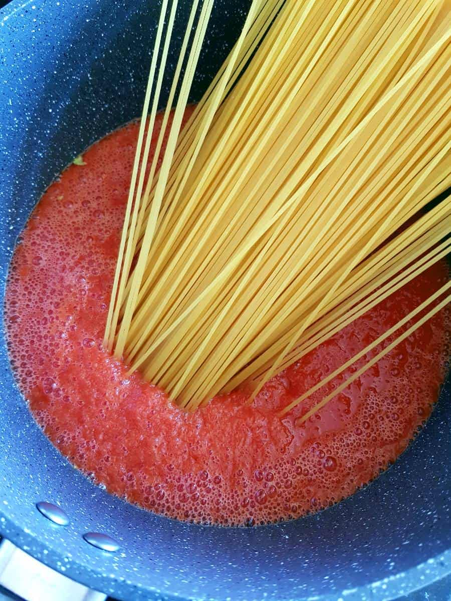 Jollof sauce and spaghetti in pot.