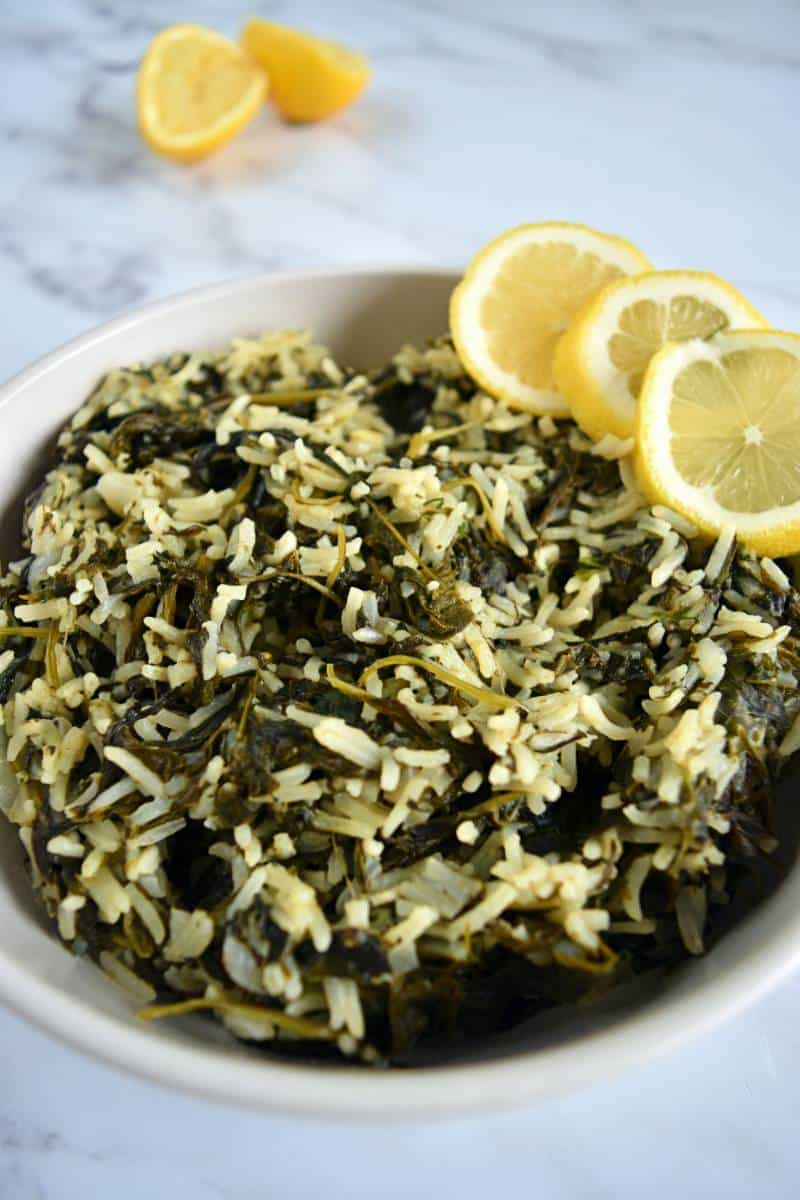 Spanakorizo in a bowl with lemon slices.