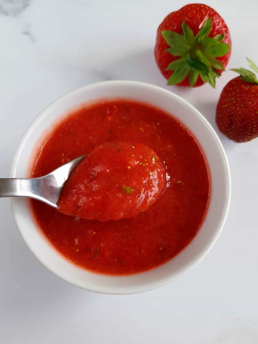 Strawberry basil sauce in a bowl with strawberries on the side.