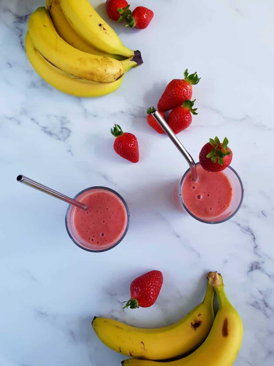 Strawberry smoothies on a table with strawberries and bananas.