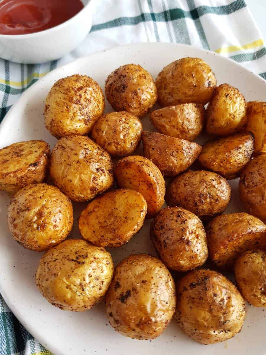 Air fryer roasted potatoes on a plate with ketchup in the back.