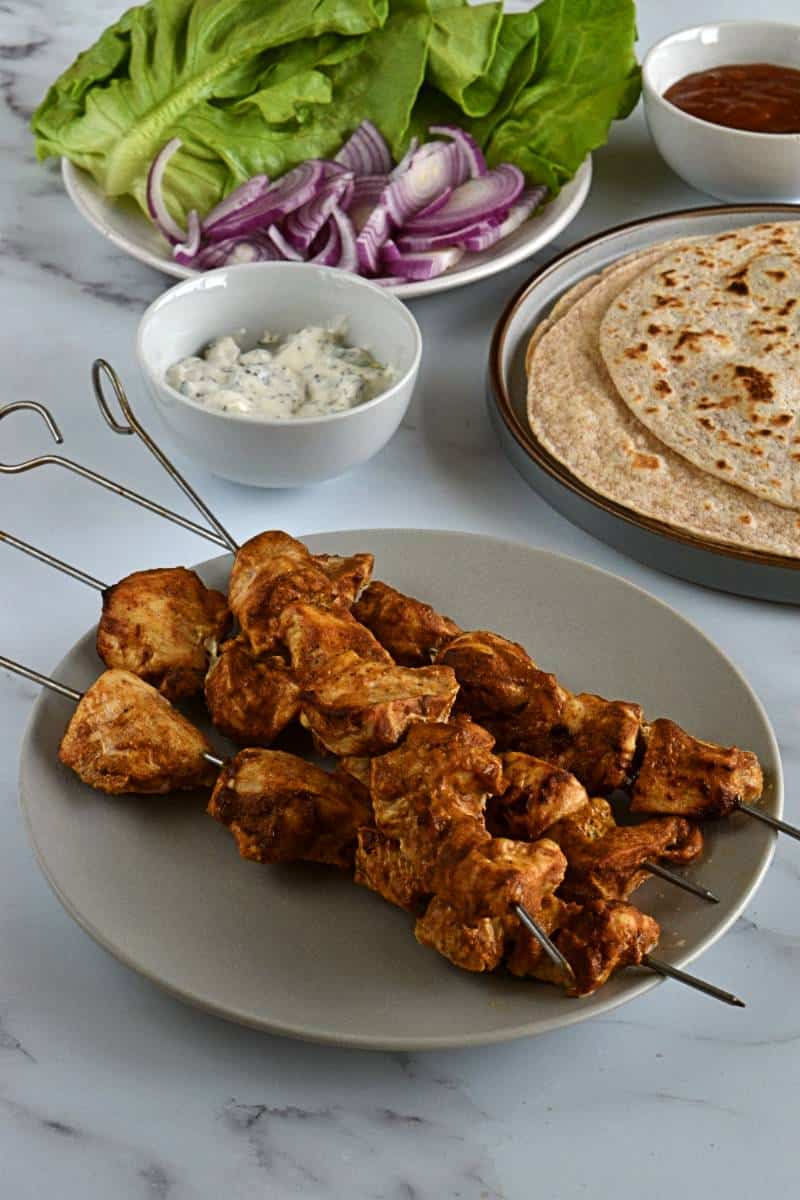 Chicken skewers tikka with salad on the side,